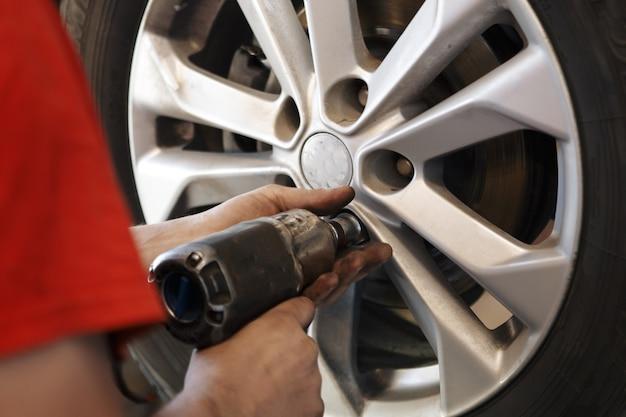 외부 타이어를 변경하는 전기 드라이버로 자동차 정비사 남자. 자동차 서비스. 손은 바퀴의 타이어를 교체합니다. 타이어 설치 개념.