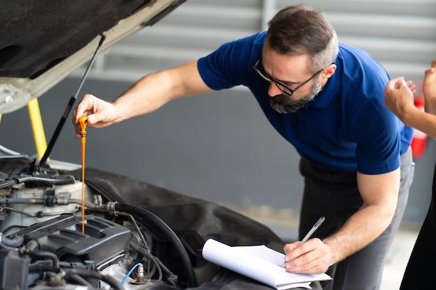 自動車エンジンのオイルレベルをチェックする自動車整備士の男性労働者。車のメンテナンスとオートサービスガレージのコンセプト。車のメンテナンスとオートサービスガレージのコンセプト。