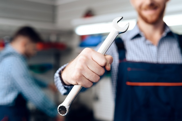 Auto mechanic posing with wrench. service station.