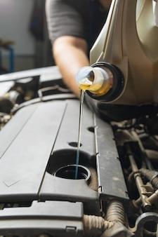 Auto mechanic pours oil into the engine