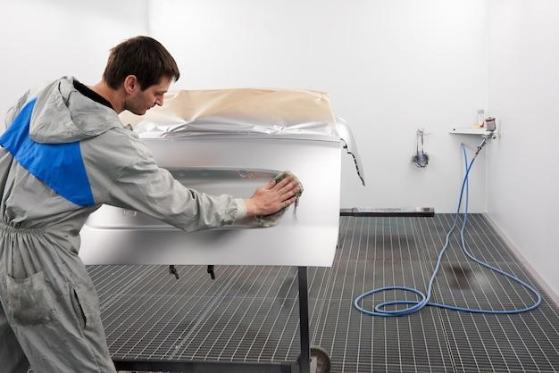 Автомеханик готовит машину к малярным работам в покрасочной кабине в автосервисной мастерской