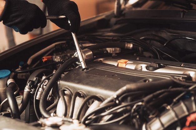 Auto mechanic repairs car. the employee carries out maintenance of the machine.