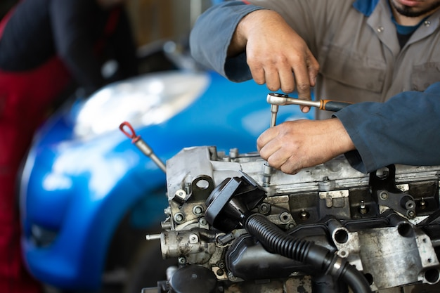 An auto mechanic repairs an internal combustion engine