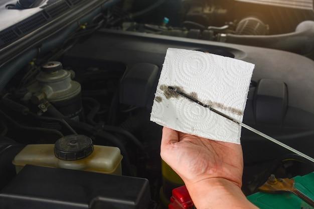 Рука автомеханика проверяет уровень и цвет моторного масла в двигателе автомобиля во время технического обслуживания.