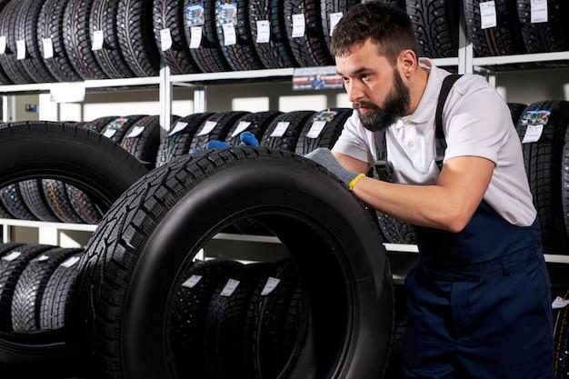 自動車整備士のセールスマンが、タイヤの品揃えを背景に自分の店でタイヤの表面を調べています。自動車、車、車両、輸送の概念