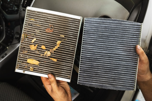 An auto mechanic shows a close-up of an old and new cabin air filter for comparison