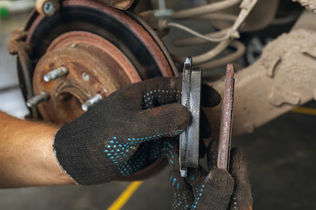 The auto mechanic shows the degree of wear of the old brake pad in comparison with the new one