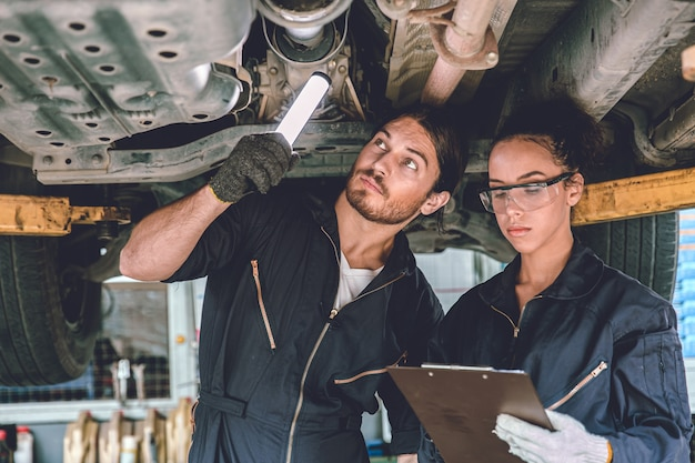 Auto mechanic team working help support together to checking under car for service maintenance in garage