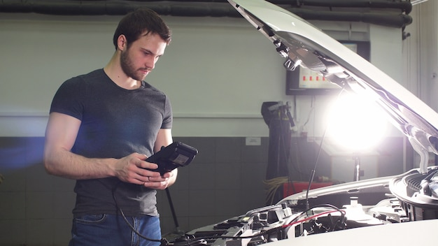 Auto mechanic testing electrical system on automobile.