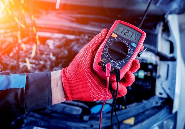 Автомеханик использует вольтметр для проверки уровня напряжения.