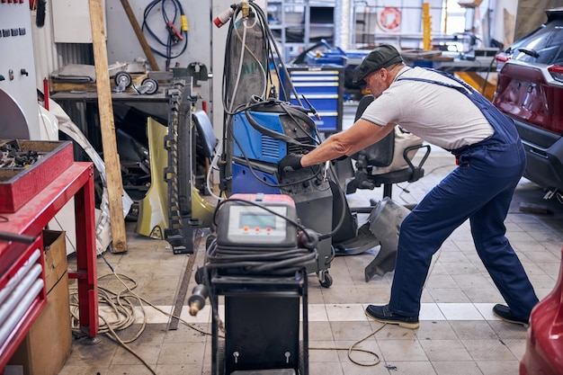 Auto mechanic using battery charger at car repair shop