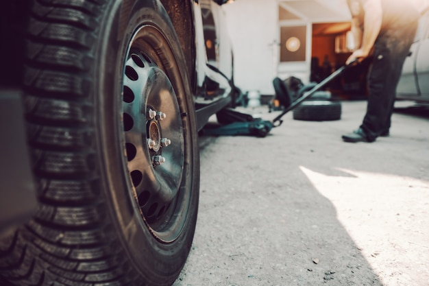 Auto mechanic using car jack at workshop. selective focus in tire.