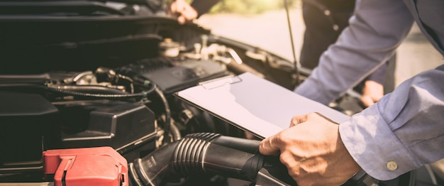 Auto mechanic using checklist for car engine systems after fixed