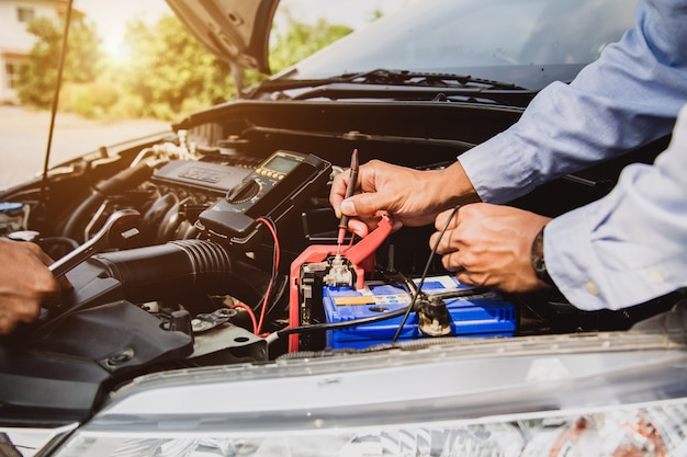 Auto mechanic using measuring equipment for checking car battery.