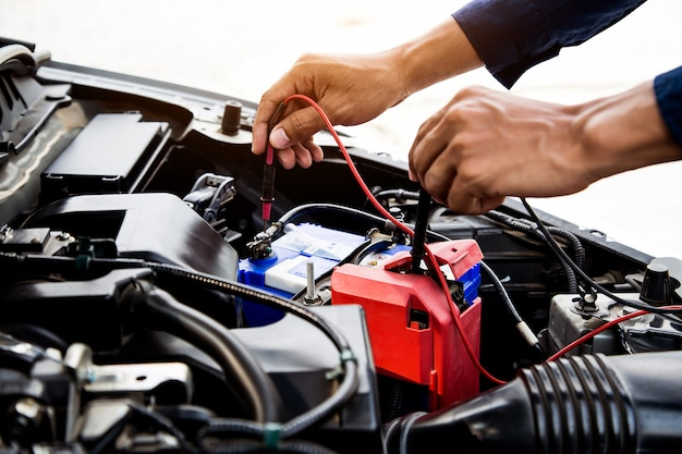 자동차 배터리 확인을 위해 측정 장비를 사용하는 자동차 정비사.