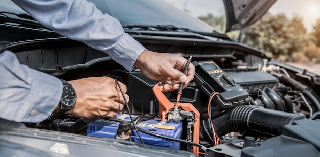Auto mechanic using measuring equipment tool to checking car battery.