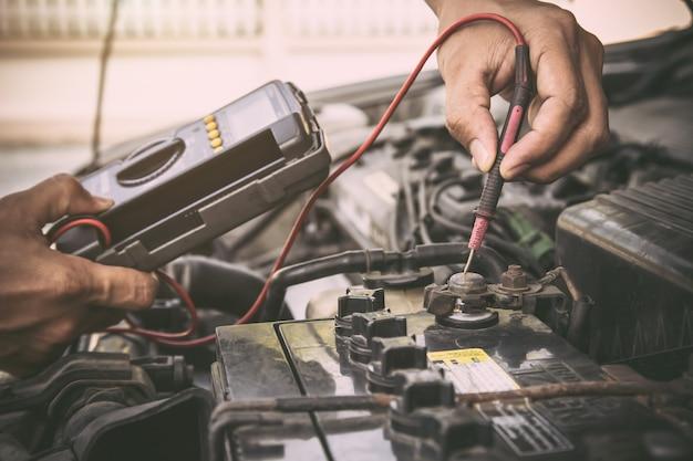자동차 배터리를 확인하기 위해 측정 장비 도구를 사용하는 자동차 정비사.