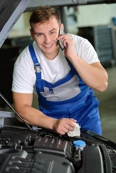 ワークショップで携帯電話を使用して自動車整備士。