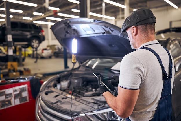 자동차 수리소에서 태블릿 컴퓨터를 사용하는 자동차 정비사