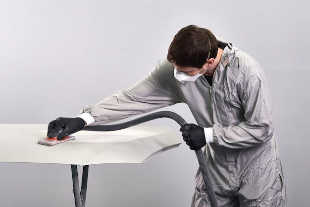 Автомеханик носить маску для полировки и полировки капота автомобиля в автосервисе