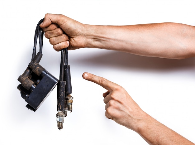 Auto mechanic with old high-voltage wires, spark plugs and ignition coil on white
