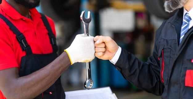 手にレンチを持った自動車整備士。ストラングルホールド。クローズアップ車修理黒人男性の手と白人男性の顧客。