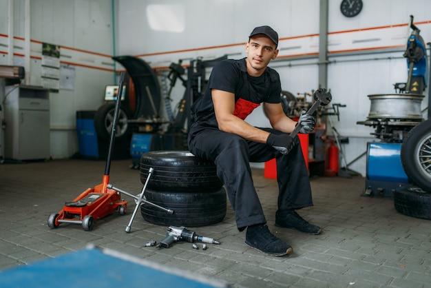 바퀴, 타이어 서비스에 앉아 렌치와 자동차 정비사. 기술자가 차고에서 자동차 타이어 수리, 작업장에서 전문 자동차 검사