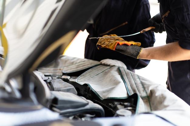 자동차 엔진에서 오일 수준을 확인하는 자동차 정비사 노동자. 자동차 정비 및 자동 서비스 차고 개념.