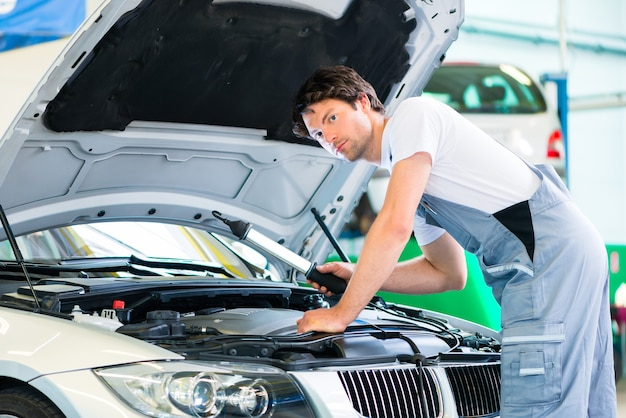 Auto mechanic working on car in service workshop