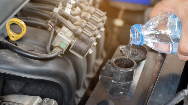 Auto mechanic working check system water and fill an old car engine, change and repair