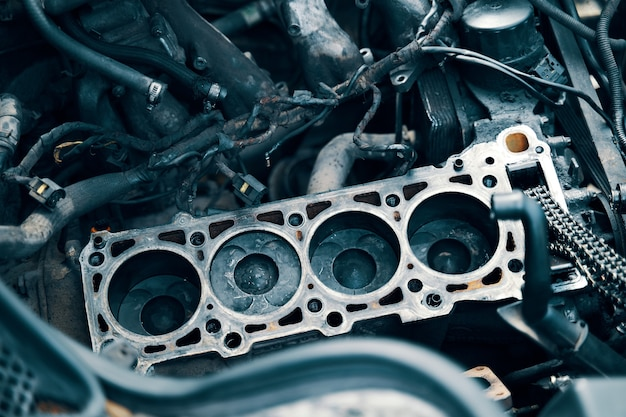 차고 수리 서비스에서 일하는 자동차 정비공은 로드 피스톤과 실린더 블록을 연결합니다.