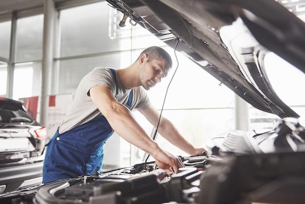 ガレージで働く自動車整備士。修理サービス。