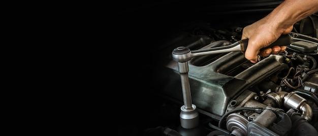 Автомеханик, работающий над двигателем автомобиля в гараже механиков ремонтные услуги свободное место для текста