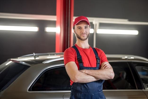 自動車整備士。帽子と作業服を着た若い成人男性が腕を胸に組んで車の近くに立っている