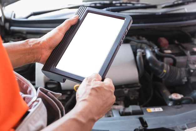자동차 정비사는 자동차 서비스에서 일하는 동안 차를 검사하고, 기술자는 차고에서 자동차 엔진 수리를 위한 체크리스트를 하고 있습니다