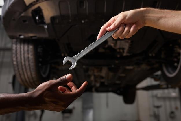 Автомеханики с ключом в ремонтной мастерской