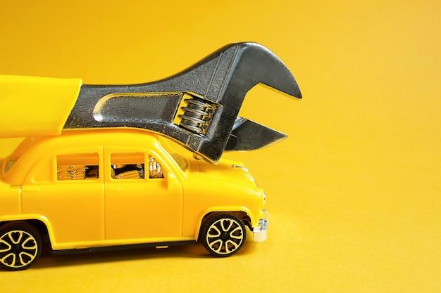 장비 및 자동차의 자동 수리 및 수리, 파손, 배관 작업, 건설을 제거하기 위해 주인의 긴급 출발. 노란색 배경에 조정 가능한 범용 키가 있는 수리 서비스 자동차.