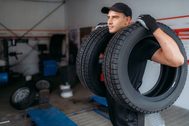 제복을 입은 자동차 수리공은 두 개의 새 타이어를 보유하고 수리 서비스를 제공합니다. 작업자가 차고에서 자동차 타이어를 수리하고 작업장에서 전문 자동차 검사