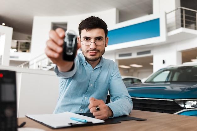 自動車のセールスマンが車のキーを提示