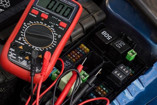 自動サービス、修理、メンテナンスのコンセプト-デジタルマルチメーターまたは電圧計テストカーバッテリー。