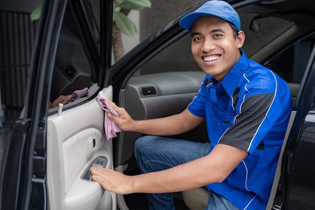 Auto service staff in blue uniform cleaning car