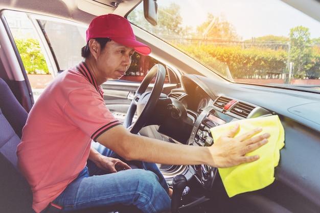 自動車サービススタッフがマイクロファイバーの布で車を掃除する