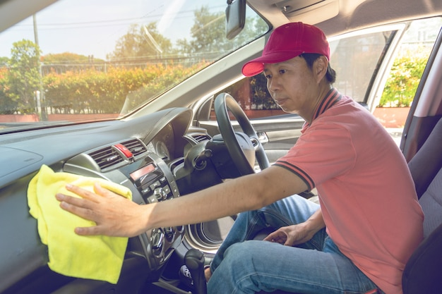 Auto service staff cleaning car with microfiber cloth
