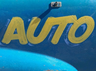 Auto yellow paint text on blue metal background