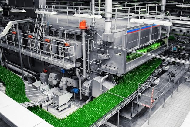 양조장의 자동화 된 컨베이어 라인. 컨베이어 벨트에 녹색 유리 병의 행. 산업 양조장.