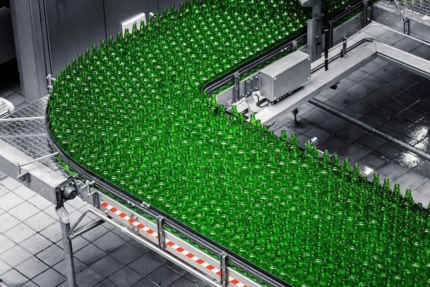 양조장의 자동화 된 컨베이어 라인. 컨베이어 벨트에 녹색 유리 병의 행.