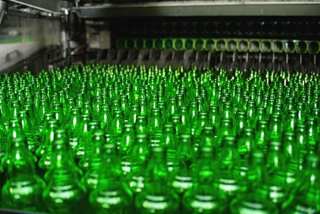 양조장의 자동화 된 컨베이어 라인. 컨베이어 클로즈업에 녹색 유리 병의 행.