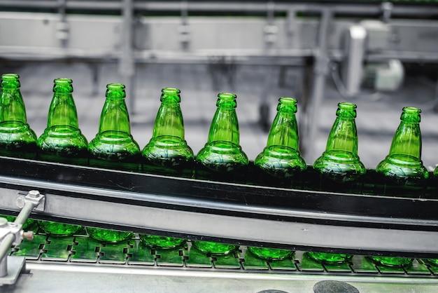 醸造所の自動コンベアライン。コンベアのクローズアップ上の緑色のガラス瓶の列。