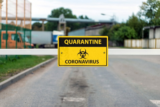 Automatic barrier with a coronavirus warning sign