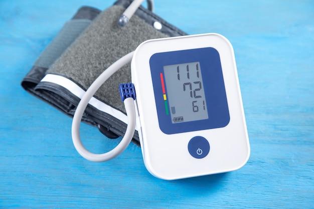 Автоматический измеритель артериального давления на синем фоне.